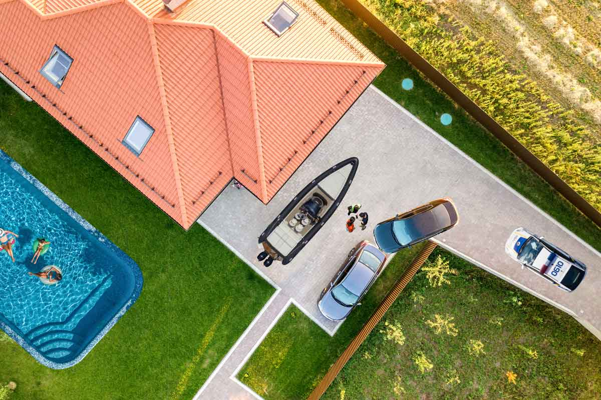 overhead view of home, pool, boat, 2 cars, and a police car