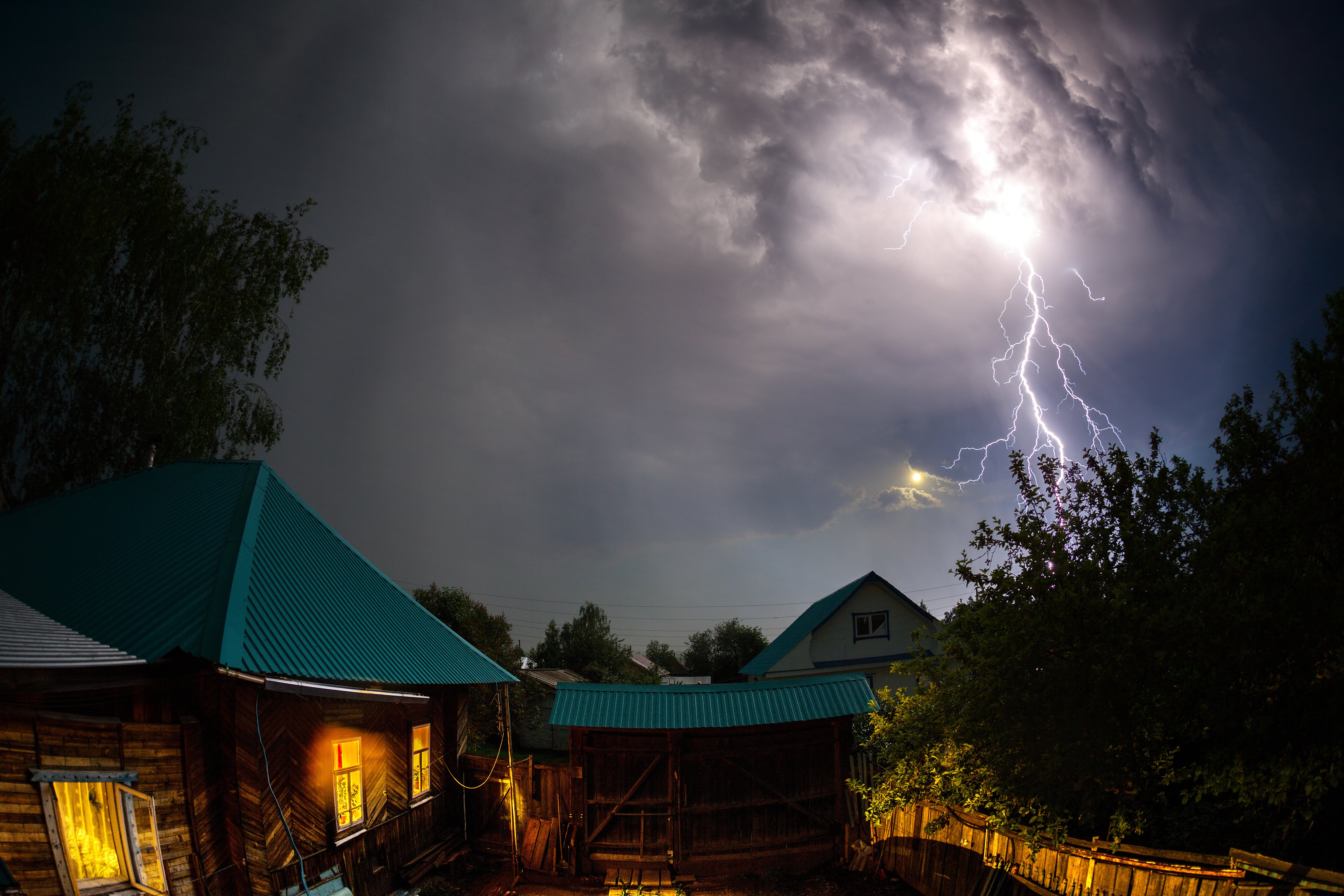 Lightning over houses in the village at night