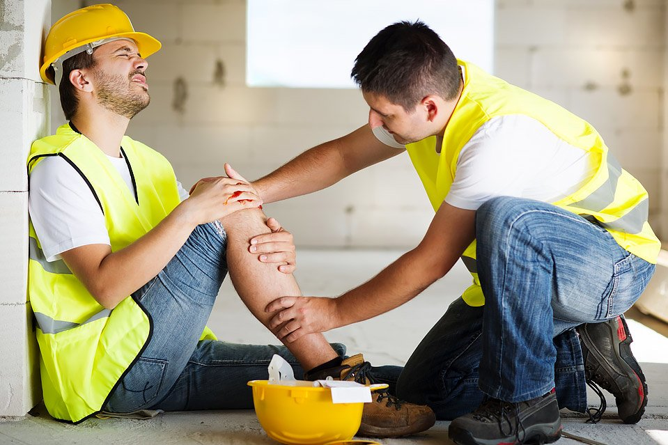 worker helping worker in pain sitting on ground