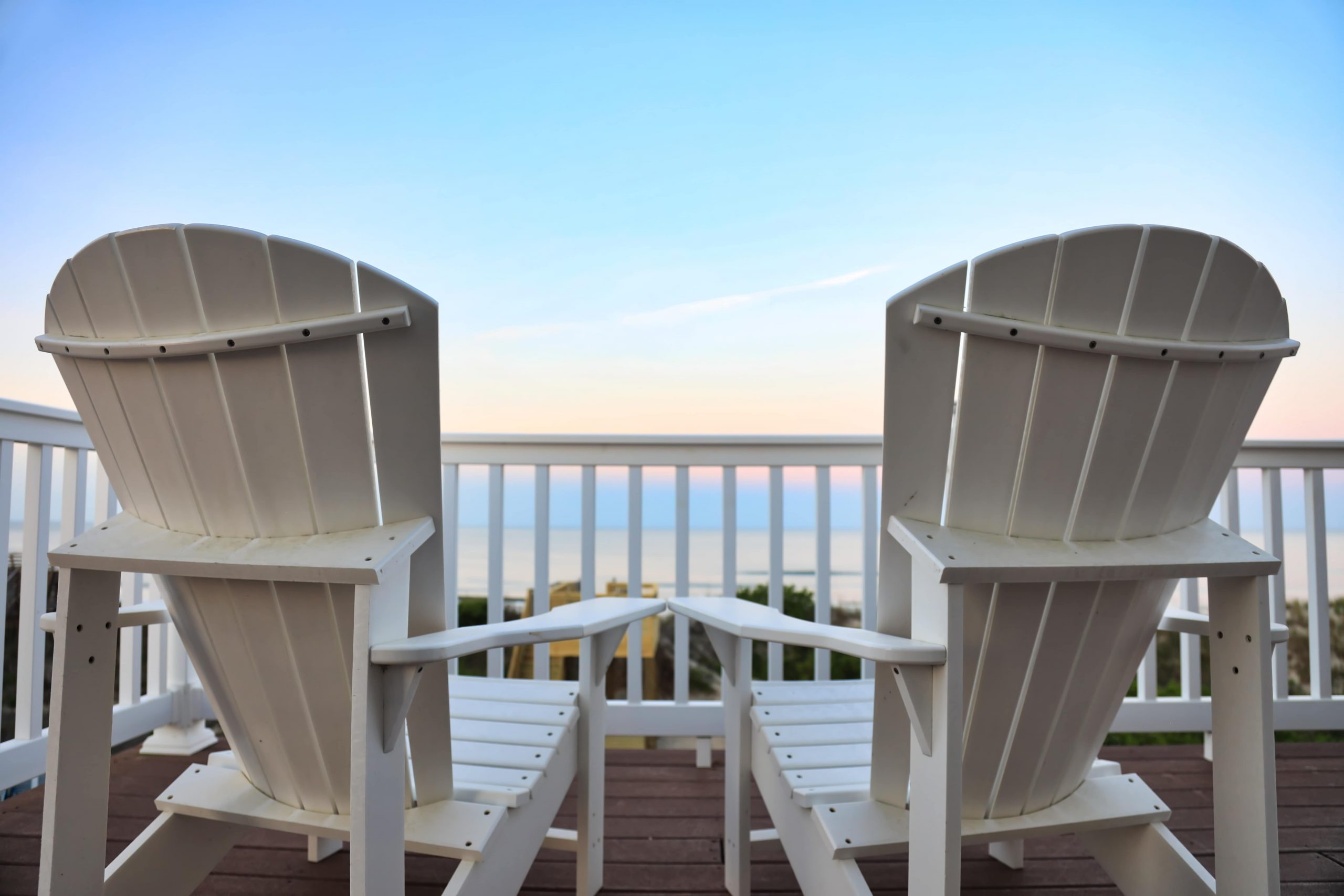 two beach chairs sitting on balony in front of ocean view